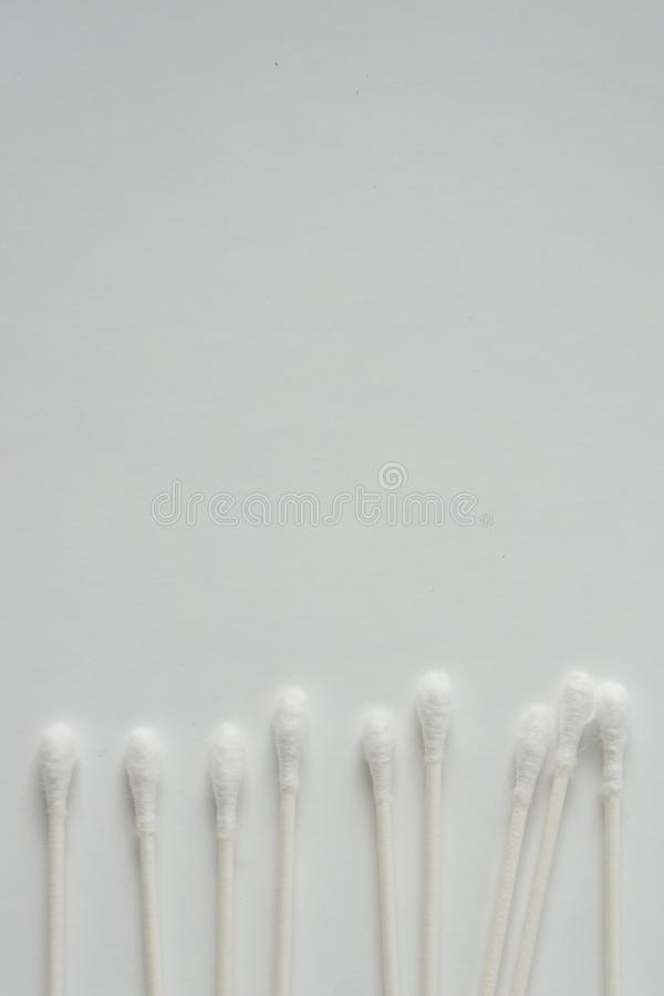 Q tip, or cotton bud swab top view on vertical white background with blank empty space for copy or text; Features best health care. Hygiene practices to clean royalty free stock photo