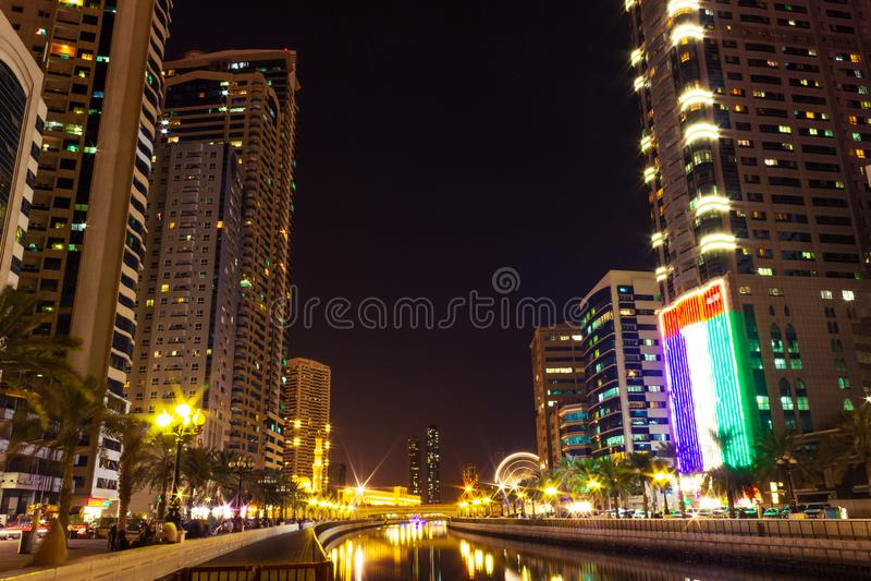 Qasba canal at night, Sharjah, United Arab Emirates. Qasba canal at night with giant UAE flag, Sharjah, United Arab Emirates stock images