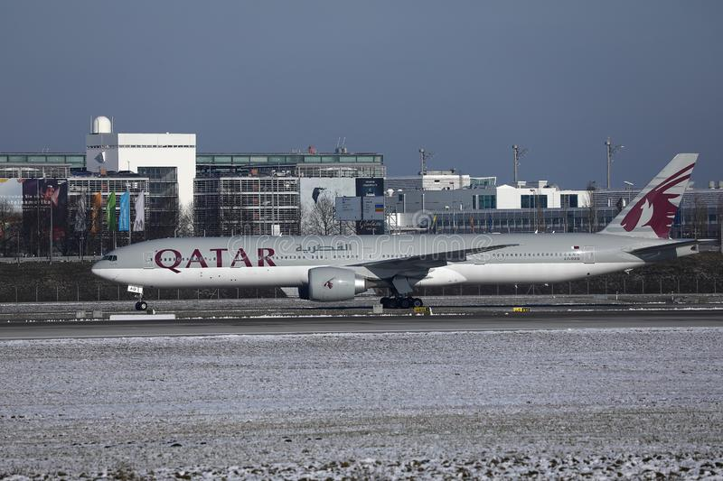 Qatar Airways plane taxiing on runway in Munich Airport, MUC, snow. Qatar Airways Plane taking off from airport, snow on runway royalty free stock photos