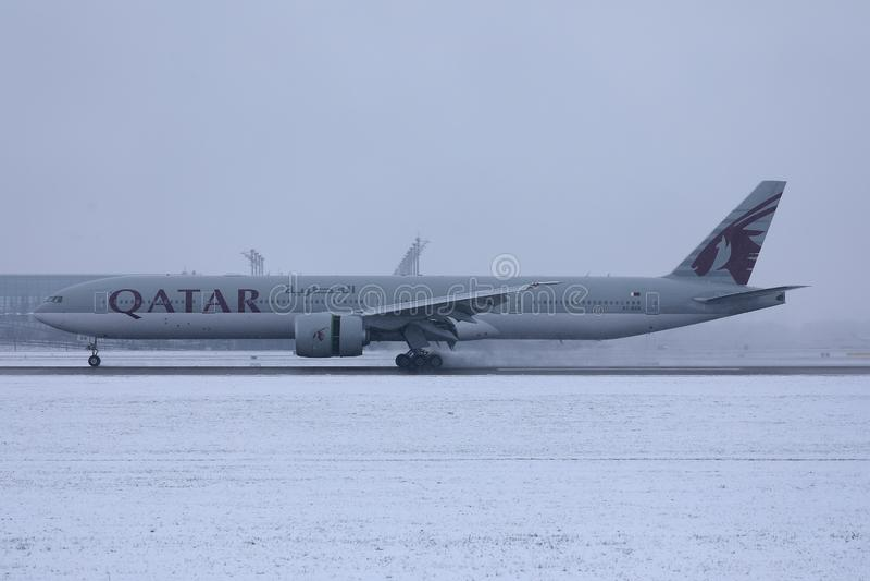 Qatar Airways plane taxiing on runway, snow. Qatar Airways Plane taking off from airport, snow on runway stock photo