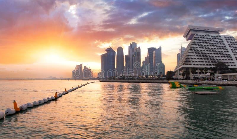 Qatar, Doha-stadshorizon bij dramatische zonsondergang stock foto's