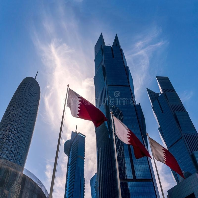Qatar Flags Sailing Surrounded with Modern Blue High Skyscrapers in Doha city, Middle East. Qatar Flags Sailing Surrounded with Modern Blue High Skyscrapers in stock photo