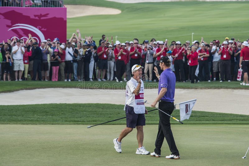 Qatar Masters 2013. DOHA, QATAR - JANUARY 26: Chris Wood is congratulated by his caddie after his magnificent eagle putt on the last hole of the US$2.5 million stock image