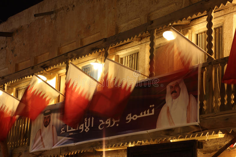 Qatari flags and portrait of Emir. Qatari flags and portrait of the Emir of Qatar in Souq Waqif, Doha. Photo taken at 6th of January 2012 royalty free stock photo