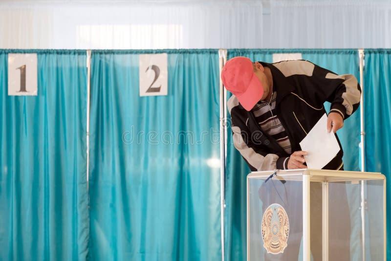 Qazaqstan, 9-ое июня 2019, избрания, голосуя, человек в красной крышке в голосуя зале кладет голосование в прозрачную коробку с стоковое изображение
