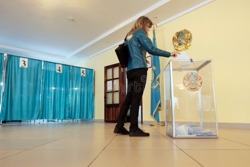 Qazaqstan, Czerwiec 9, 2019, wybory, głosuje Młoda dziewczyna w głosuje sali obniża a w tajnym głosowaniu w przejrzystym pudełku  zdjęcie stock
