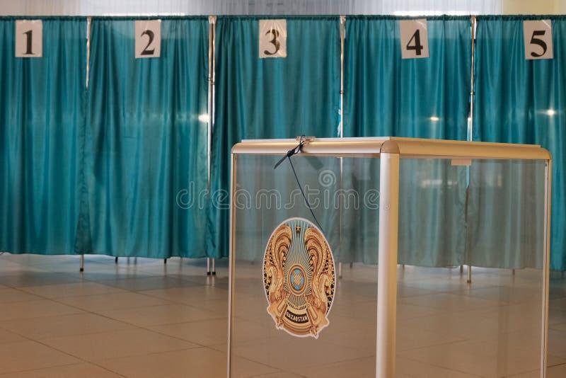 Qazaqstan am 9. Juni 2019 Klarsichtschachtel mit dem Emblem von Kasachstan Pr?sidentschaftswahlen Abstimmungsraum auf dem Hinterg lizenzfreies stockfoto