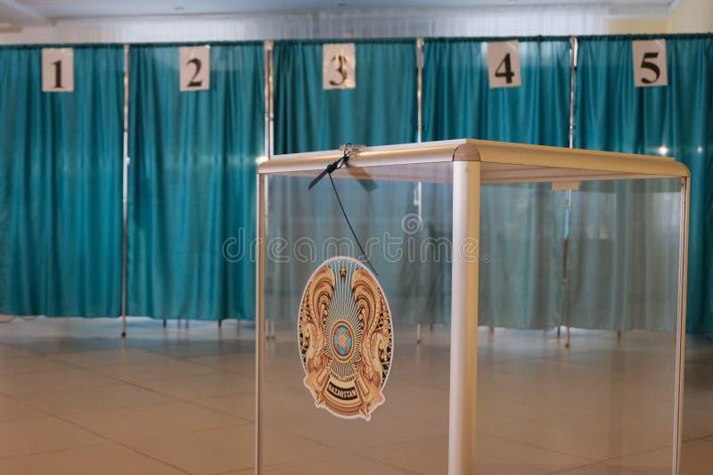 Qazaqstan, o 9 de junho de 2019, eleição do presidente de Cazaquistão Caixa transparente com o emblema Sala de votação no fundo fotos de stock