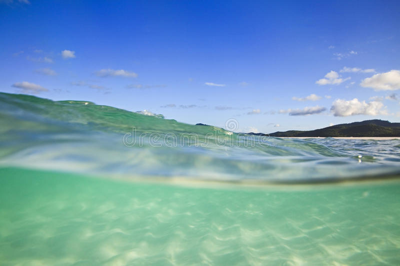 QE Whitehaven submerged. Half-submerged in clean transparent green salt water of coral sea at white silica Whitehaven beach on Whitsunday island of Great Barrier stock photos