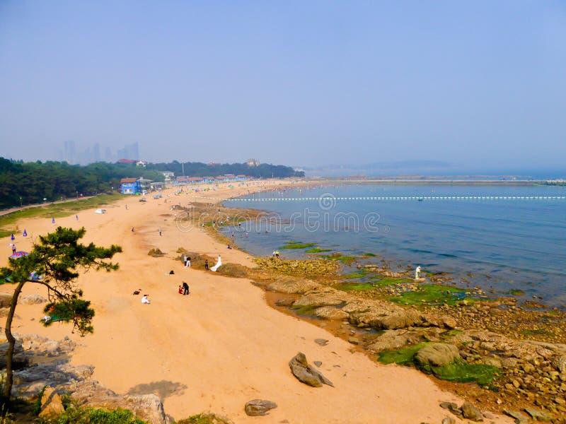 Qingdao city bathing beach. Tourists walking on the bathing beach near fushan bay with modern buildings background in qingdao city shandong province China royalty free stock image