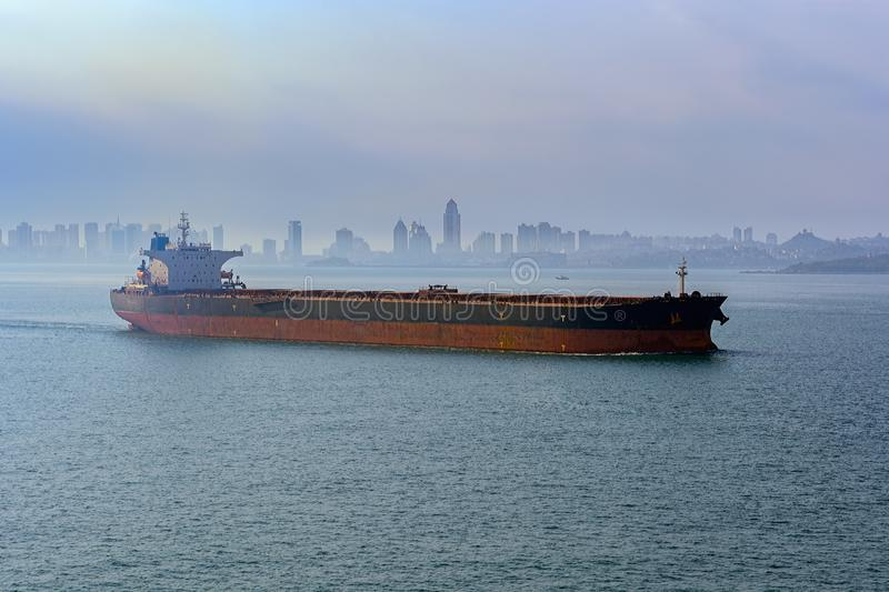 Qingdao waterfront. Giant bulk carrier vessel in ballast leaves the port of Qingdao along Jiaozhou Bay shore in the morning fog royalty free stock image