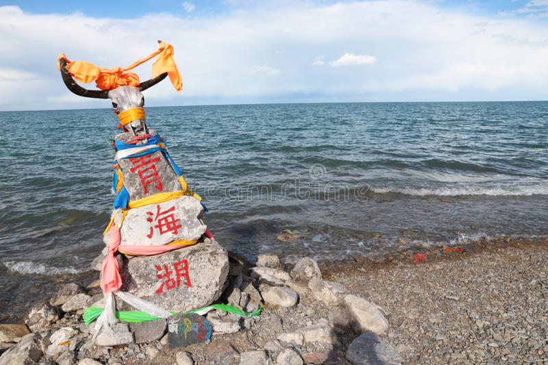Qinghai Lake in 2015. Stones and flags on the shore of Qinghai Lake during the 2015 pilgrimage of Tibetan buddhists stock image
