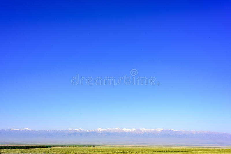 In Qinghai province of China, blue sky, grassland and snow-capped mountains constitute a beautiful picture royalty free stock photos