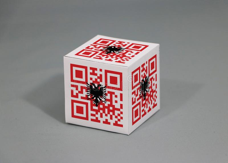 QR code set the color of Albanian flag painted on the cubic. The concept of export trading from Albania. Paper box packaging for put products stock photography