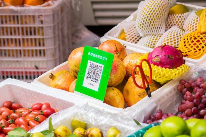 Qr koder för cashless betalningställningar över ett fruktbås arkivfoto