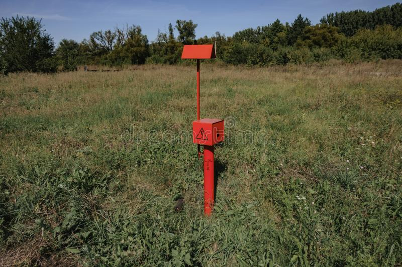 Qred electric cable stands in the field. Red electric cable stands in the field, voltage, electricity, current, technology, construction, high, energy stock photography