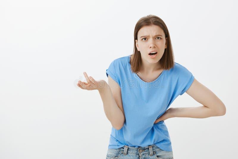 Qué él su punto, tipo Mujer atractiva enfadada cabreada, doblando hacia cámara con la entrega en cadera y la palma aumentada imagen de archivo libre de regalías