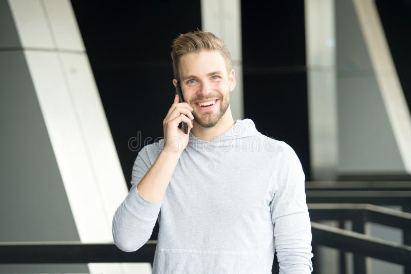 Qué grandes noticias Hombre con el fondo urbano del smartphone de la llamada de la barba Smartphone feliz del uso de la sonrisa d fotos de archivo libres de regalías