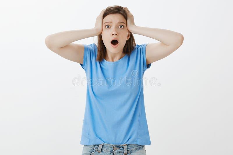 Qué le tienen hecho, oh no Mujer atractiva devestated Shocked en el equipo casual, jadeo, colocándose con la boca abierta y foto de archivo libre de regalías