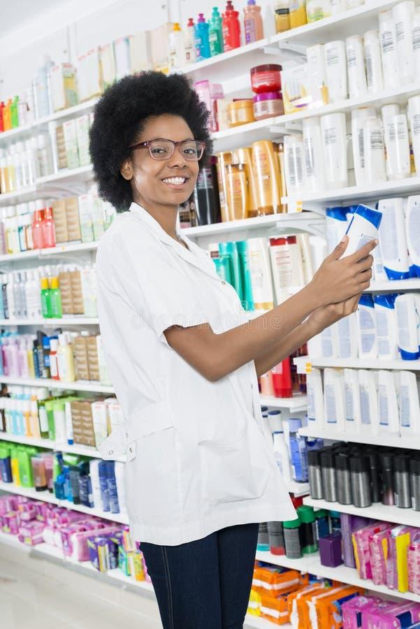 Químico de sexo femenino Holding Shampoo Bottle en farmacia imágenes de archivo libres de regalías