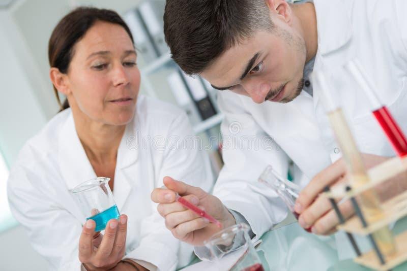 Químico de sexo masculino joven que sonríe mientras que pipeta de la prueba del control en laboratorio imagen de archivo libre de regalías