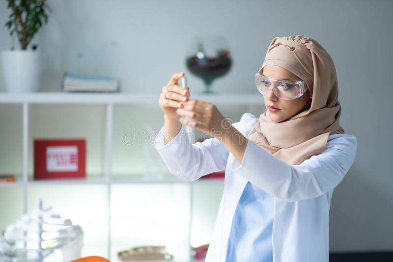 Químico elegante que lleva los vidrios protectores que sostienen el tubo de ensayo fotos de archivo libres de regalías