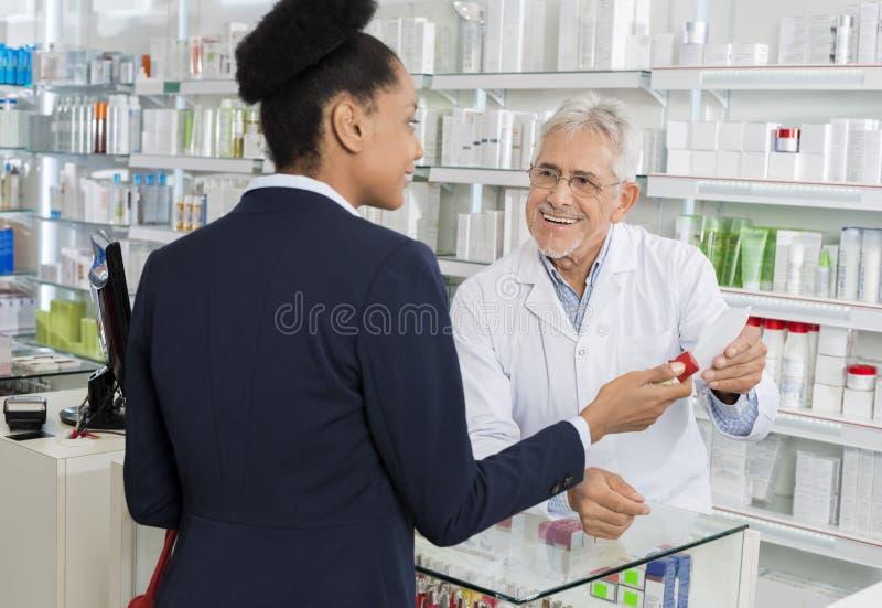 Químico Holding Prescription Paper ao olhar Businesswoma foto de stock