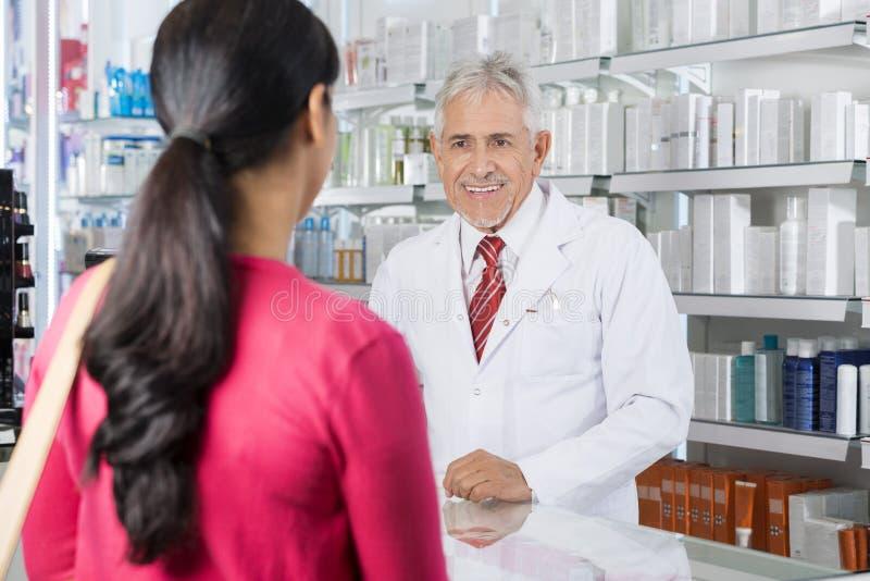 Químico Looking At Customer na farmácia imagem de stock royalty free