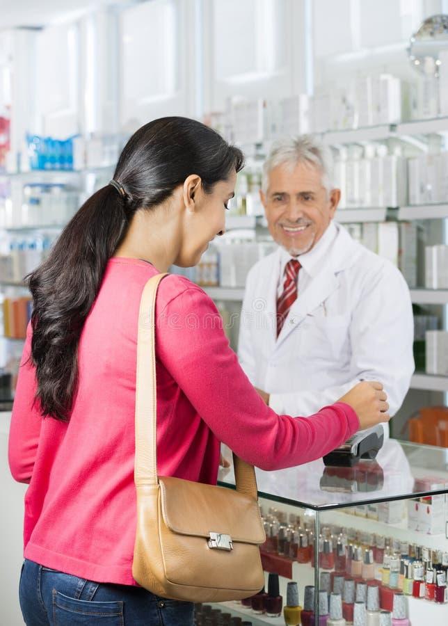 Químico Looking At Customer que faz o pagamento no contador foto de stock