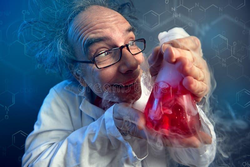 Químico louco que olha lovingly o tubo de ensaio fotos de stock