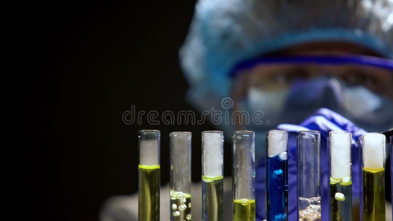 Qu?mico que comprueba la reacci?n en tubos de ensayo, experimento secreto del laboratorio, biolog?a fotografía de archivo