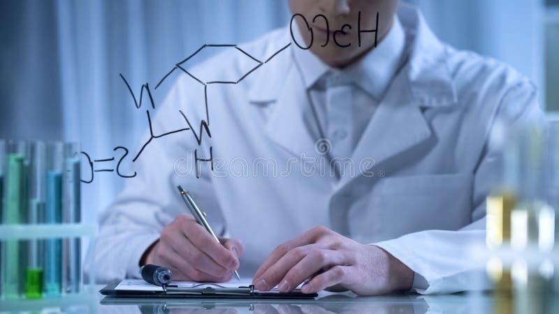 Químico que escreve a fórmula no dobrador do vidro e do cartão, pesquisa na cosmetologia fotografia de stock