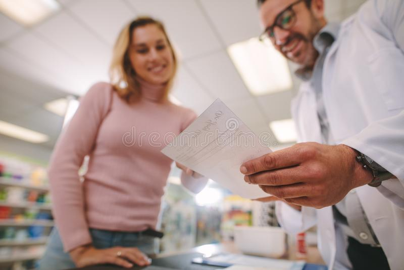 Químico que explica una prescripción al cliente fotografía de archivo libre de regalías