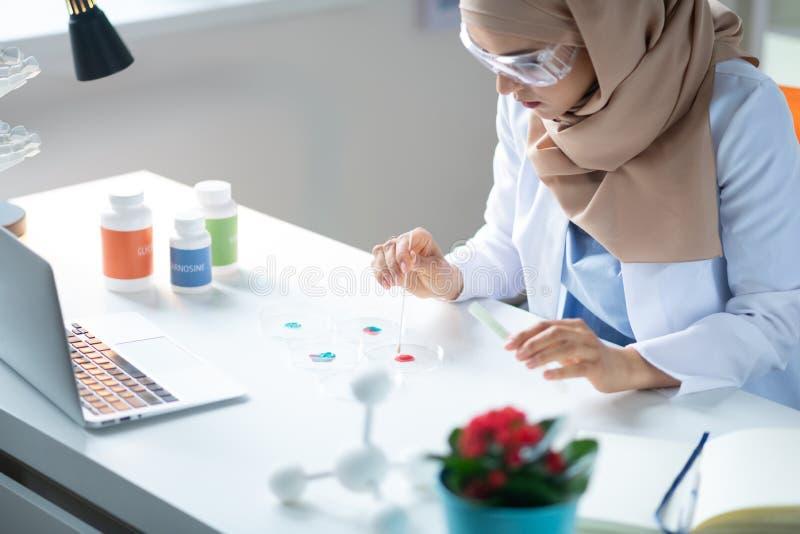 Químico que lleva los vidrios protectores que hacen algunos experimentos imágenes de archivo libres de regalías