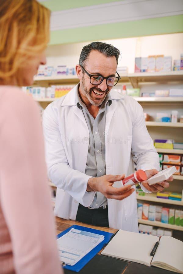 Químico que sugiere la droga médica al comprador en la farmacia fotografía de archivo libre de regalías