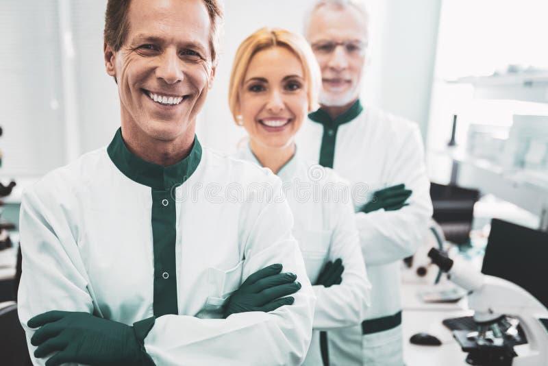 Químicos profesionales que sonríen mientras que alcanza grandes resultados fotos de archivo libres de regalías