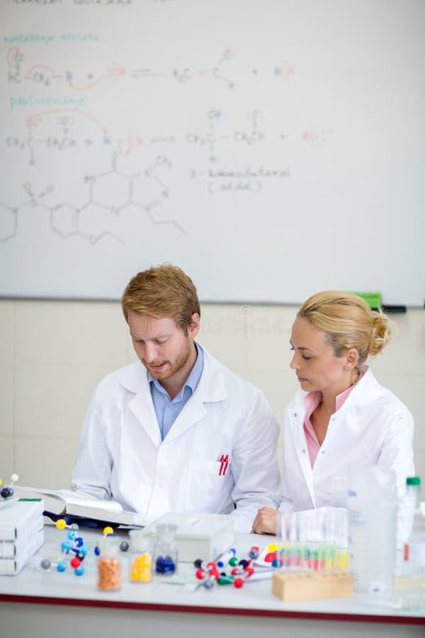 Químicos que preparam a leitura na sala de aula fotos de stock royalty free