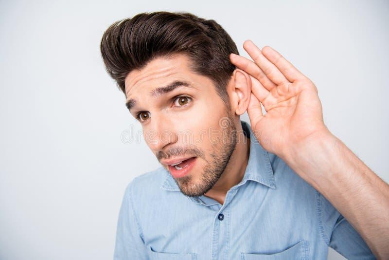 Qu'avez-vous dit ? Fermez la photo d'un type étonné qui se sent curieux tenez la main près de l'oreille écoutez des rumeurs incro photos stock