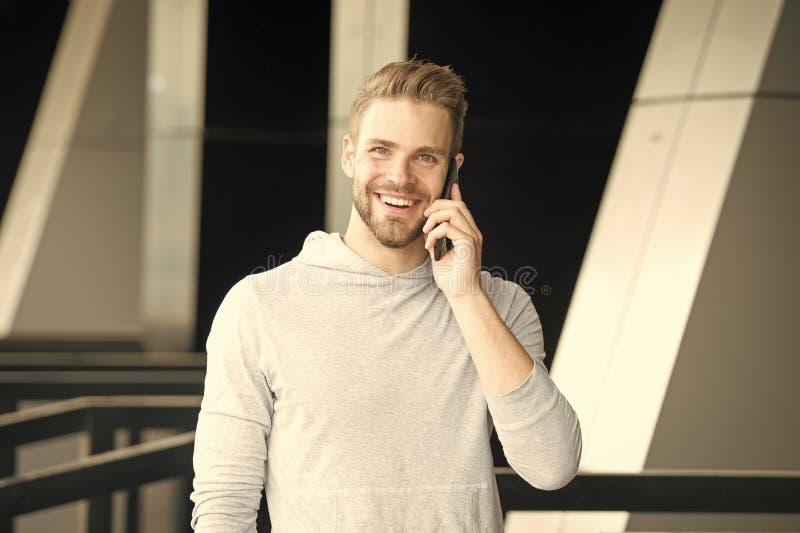 Qu? grandes noticias Hombre con el fondo urbano del smartphone de la llamada de la barba Smartphone feliz del uso de la sonrisa d imagen de archivo libre de regalías
