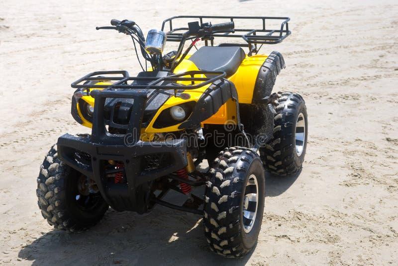 Quad bike. Yellow quad bike on sand royalty free stock image