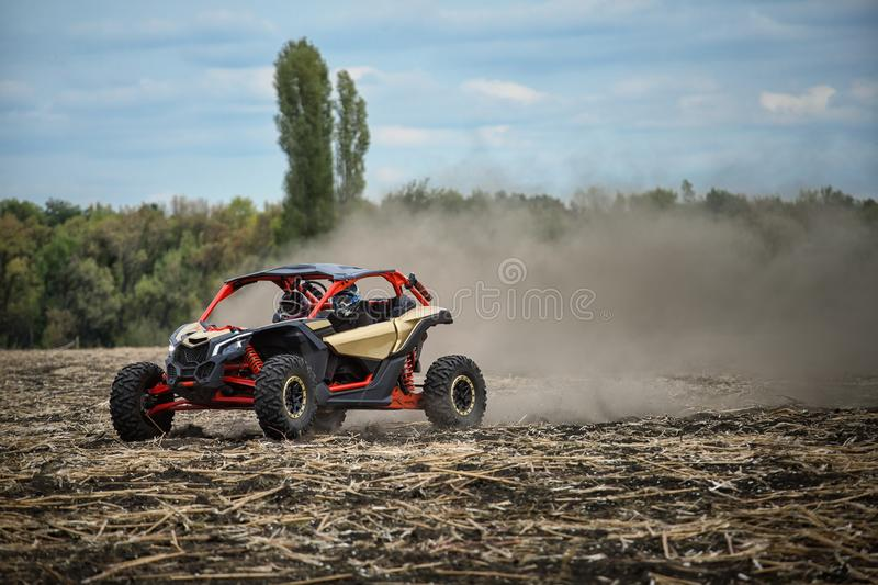 Quad bike is racing along an oblique field stock photo