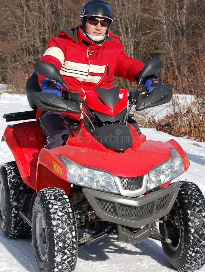 Quad bike rider on snow stock photos