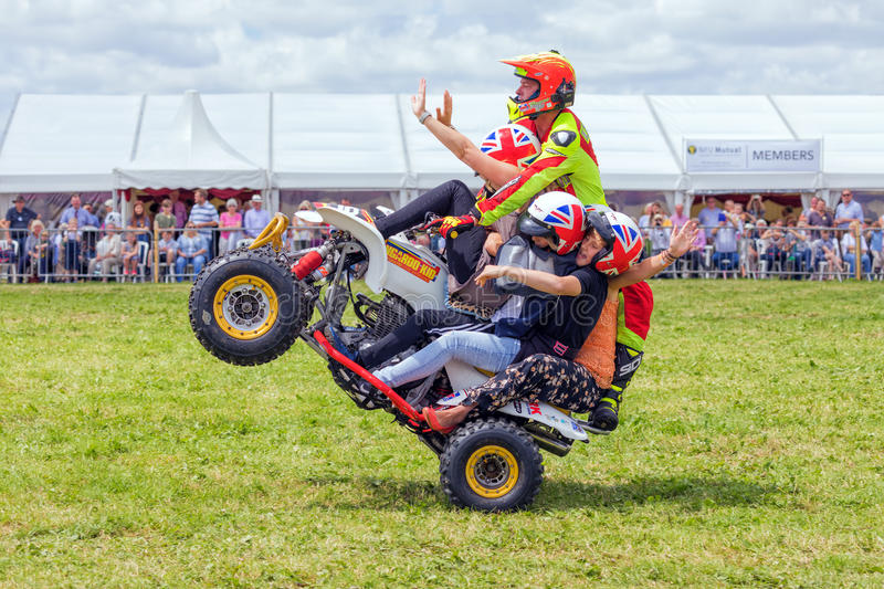 Quad bike wheelie stunt. The Kangaroo Kid, Matt Coulter, pulling a wheelie with four members of the public on his quad bike at the Hanbury Countryside Show in royalty free stock images