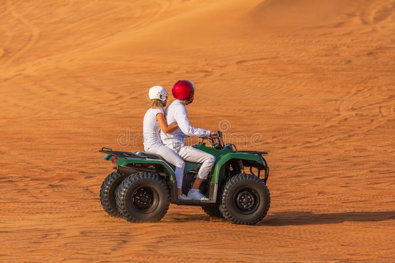 Quad Biking Dubai Adventure Tour – Young copule of tourists having fun on Quad Bike Riding in dunes of Dubai stock photography