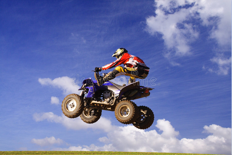 Quad jump. Ing high, blue sky, white clouds as background stock photo