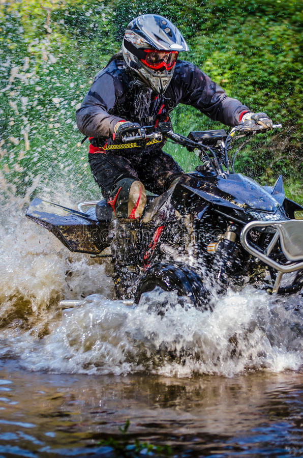 Quad rider through water stream royalty free stock image