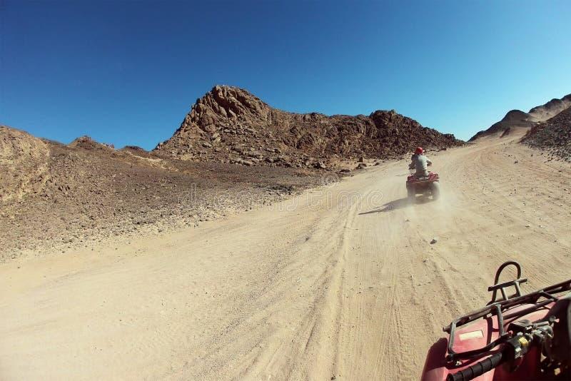 Quadbike está montando en el desierto imagenes de archivo