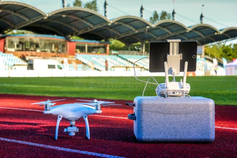 Quadcopter bianco con quattro motori ed eliche che stanno nel grande stadio fotografia stock libera da diritti