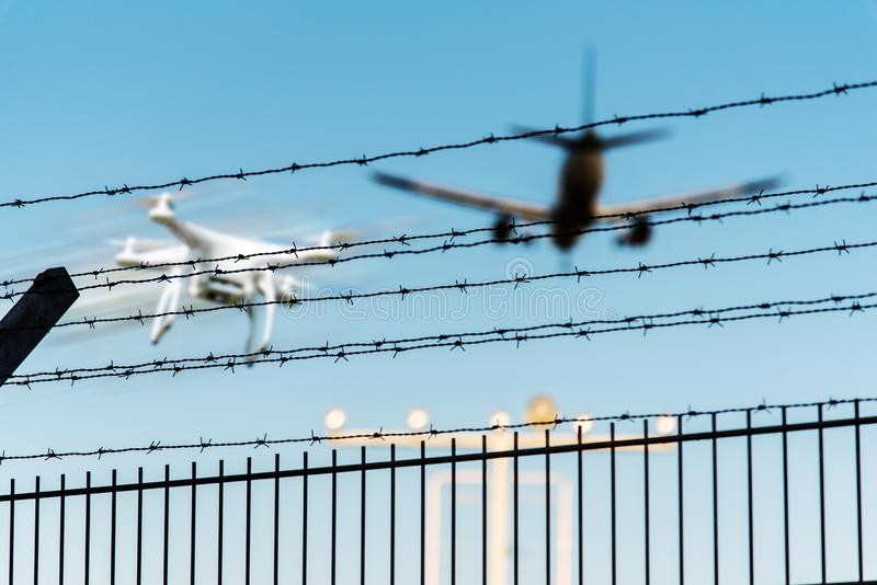 Quadcopter-Brummen im Flug nah an nähernder Flughafenrollbahn des Flugzeuges stockbild