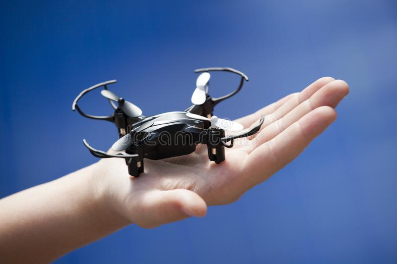 Quadcopter children hand blue background stock photos